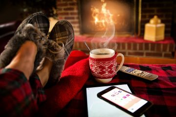 A person sits near an open fire with her feet up on a coffee table covered in a red and black rug. On the table are a steaming hot cup of coffee, a mobile phone, a blank notepad and a remote control.