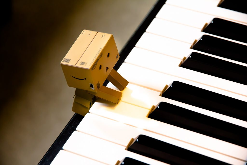 A cute wood human-looking figure rests up against the piano and plays a white note in each hand.