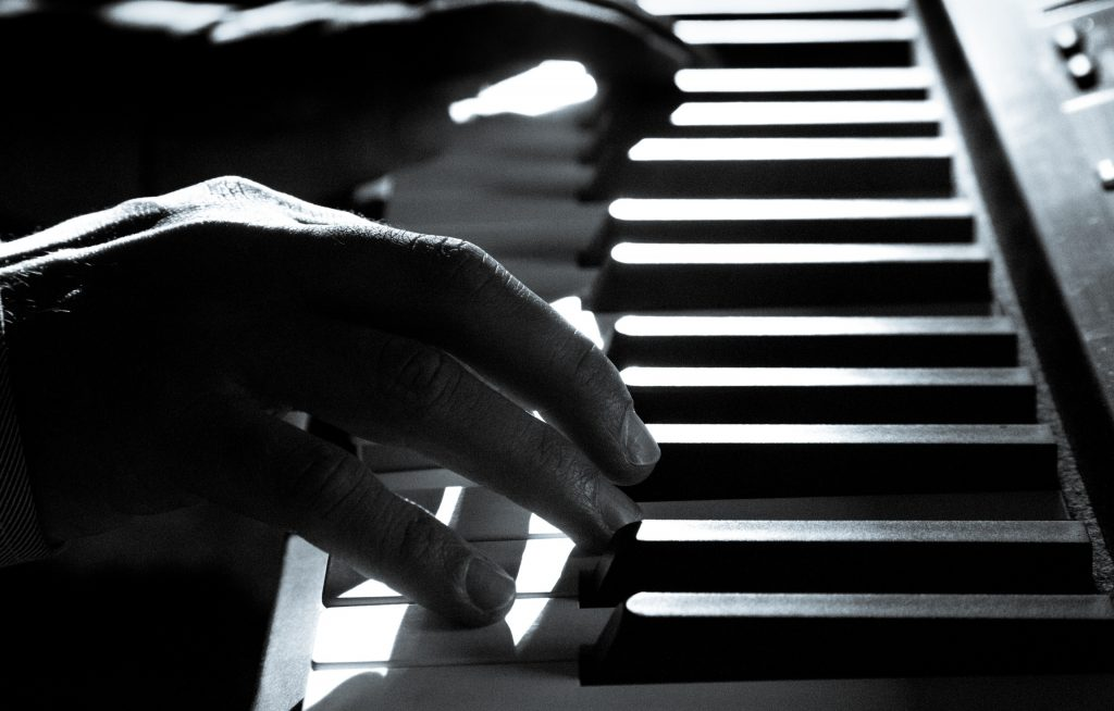 A black and white photo of proficient hands playing a piano keyboard.