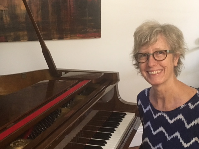 A photo of Linda Magson at her grand piano. Linda Magson Music is all about working with adults who want to learn to play the piano for the first time, or to return to music after a period of not playing. Linda is wearing an electric blue long-sleeved top with white horizontal jagged lines. She has short, textured blond hair and is looking directly at you, smiling.