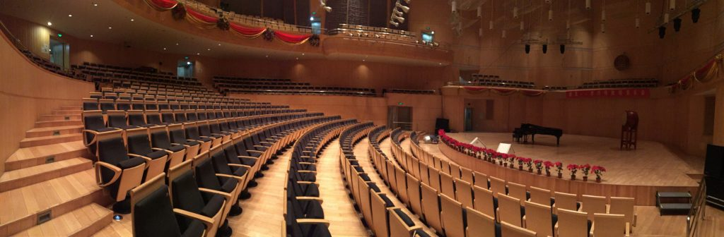 An empty grand concert hall, with wooden seats and floor. The stage is set with a grand piano. Preparing yourself to perform with confidence makes the difference.