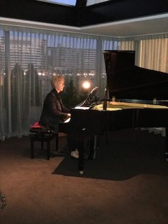 Linda Magson at the piano, Quay Restaurant. Linda is a Classical pianist for small events in Sydney It is dusk and she sits at the black grand piano in the corner of an open lounge area of the restaurant.
