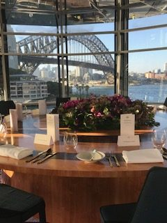 View from the Quay Restaurant, Sydney, showing a round table overlooking Sydney Harbour Bridge. It is the perfect venue for a Classical pianist for small events in Sydney.